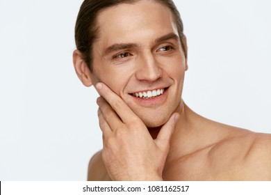 Men Face Care. Man Touching Smooth Skin After Shaving