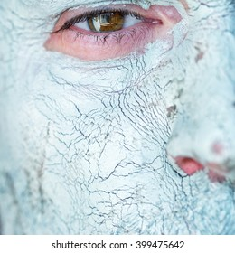 Men face closeup on facial blue clay mask. Treatment and care for the face skin