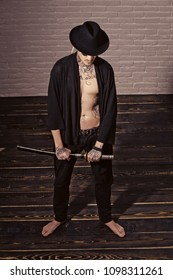 Men face skin care. Portrait Men face in your advertisnent. Warrior in black hat and open clothes showing tattooed torso. Man with sword standing on wooden floor barefoot, top view. Honor and dignity