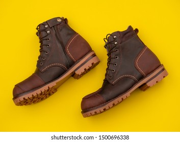 Men fashion brown boots with zipper isolated on a yellow background. Steel toe Boots fashion design by custom made for bikers.