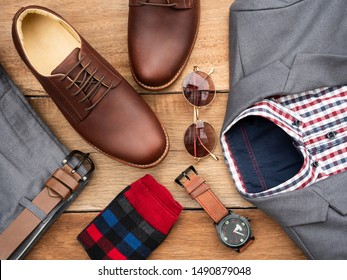 Men fashion casual clothing set and accessories isolated on wooden background include derby shoes, gray suit, pants, belt, sunglass, sock and scottis office shirt. Flat lay, top view