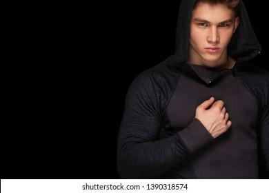 Men fashion. Close-up portrait of a brutal and fit man. Athlete bodybuilder on black background.