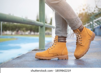 Men fashion in leather boots, Close up view on man's legs in gray jeans and yellow leather boots. - Shutterstock ID 1859842219