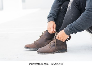 Men fashion legs in black jeans and brown leather boots on white fe18e9f00