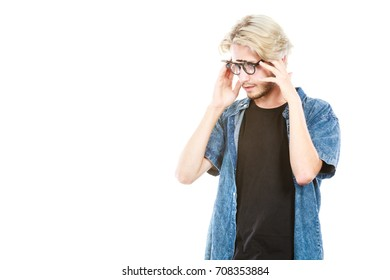 Men fashion, modeling concept. Hipster man looking for something wearing jeans outfit and eccentric glasses, hand close to his head studio shot, isolated