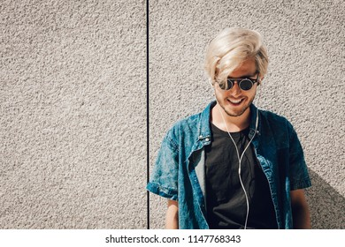 Men fashion, technology, urban style clothing concept. Hipster guy standing on city street wearing jeans outfit and eccentric sunglasses listening to music and holding phone