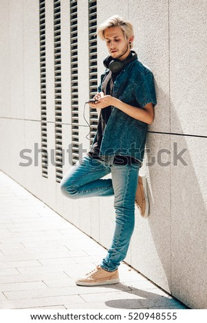 0a3dd4d38f0e Men fashion, technology, urban style clothing concept. Hipster guy with  headphones standing on
