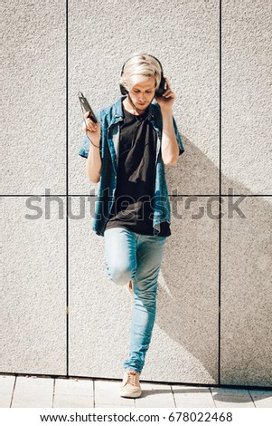 09f619f7268e Men fashion, technology, urban style clothing concept. Hipster guy standing  on city street