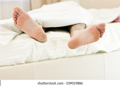 Men feet alone in a bed. Bright one-color linen.