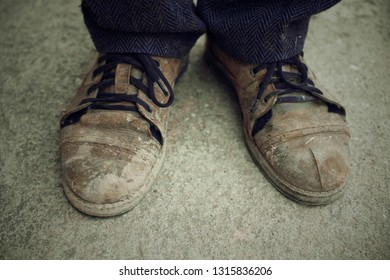 Men is feet in old torn shoes