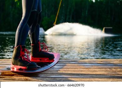 men feet on a wakeboard on forest landscape