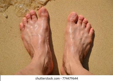Men feet stand on beach