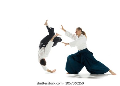 Men fighting at Aikido training in martial arts school. Healthy lifestyle and sports concept. Man with beard in white kimono on white background. Karate man with concentrated face in uniform. Isolated