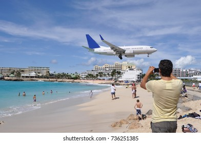 Men Filming the Airplane Landing above Maho Beach in St. Maarten Island