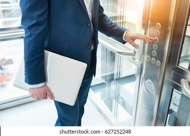 Men finger presses the elevator button. Businessman is a lift. high floor