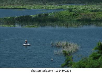 Men fishing on rubber boat in a lake