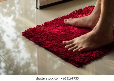 Men foot on red doormat in home.