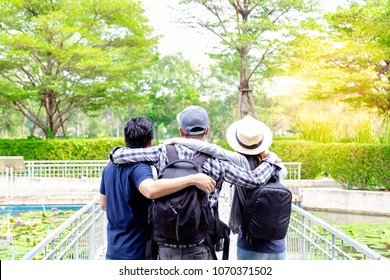 Men and girl are brotherhood when they have holiday, they love to go beautiful place together. Handsome men, lovely woman is looking at copy space and admiring nature. They are hugging together.