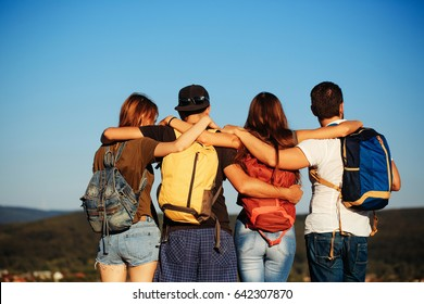 men and girls or pretty women watching idyllic landscape on sunny, blue sky. Friends or tourists with colorful backpacks on mountain top. Back view. Summer vacation. Travelling, hiking