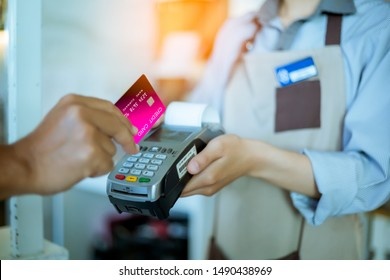 Men give credit cards to female employees to pay for goods.