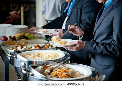 men in gray suits choosing food at a banquet
