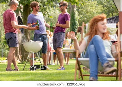 Men grilling shashliks and drinking beer during outdoor party. Blurred woman in the foreground