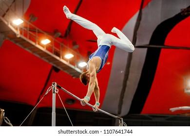 men gymnast exercises on high bar in artistic gymnastics