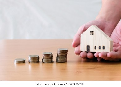 Men hand hold, giving wood house beside increasing money, coin stack on wood table. Saving plan to buy property, house. Personal financial concept for own a house. with copy space for text