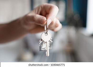 Men hand holding key with house shaped keychain. Modern light lobby interior. Mortgage concept. Real estate, moving home or renting property.