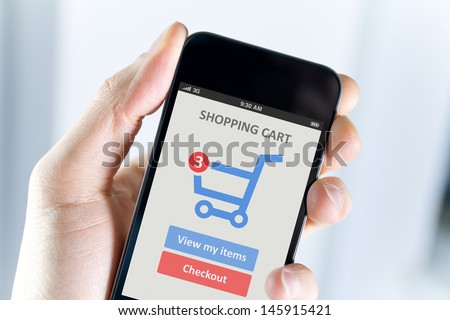 Men hand holding modern mobile phone with online shopping application on a screen.