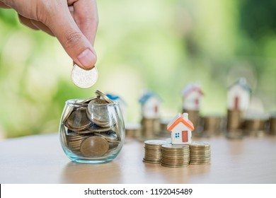 A men hand holding stacking gold coins and house model, saving money for buying a new home and investment with real estate concept.