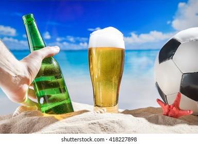 Men hand take bottle of beer in sand at beach near soccer ball