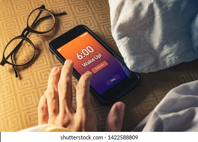 Men hand trying to snooze the alarm clock on smartphone.