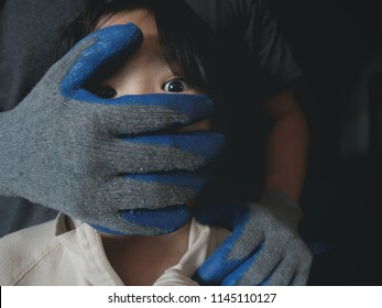 Men hand is wearing glove covering child girl mouth. Concept of violence or kidnapping. Dark mood.