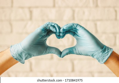 Men hands in protective gloves showing heart symbols in hospital. Doctor surgeon in medical gloves gesturing love sign with fingers. Arms in heart shape. Health care, charity, COVID-19 protection