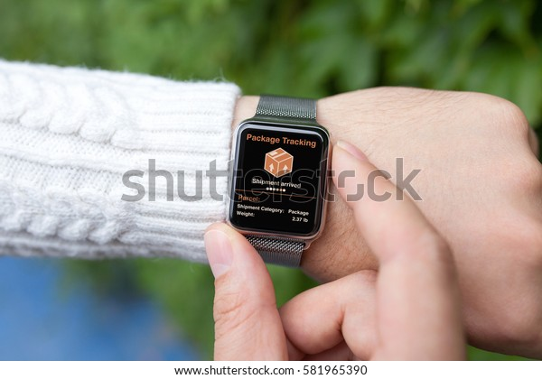 men hands smart touch watch with app tracking delivery package on the street