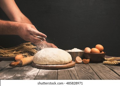 Men hands sprinkle a dough with flour close up