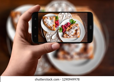 Men hands  takes photography of food on table with phone. Apple pie with raspberries and mint. Smartphone photo for post on social networks.