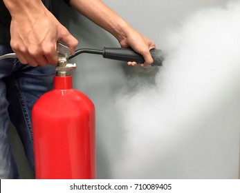 Men hands using red fire extinguisher
