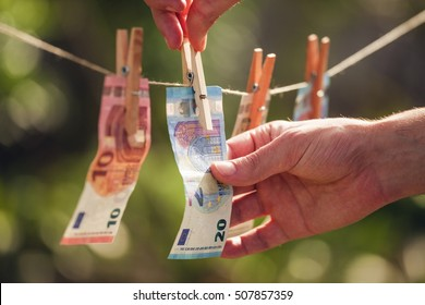 Men is hanging euro bills on clothesline on a natural background. Money concept.