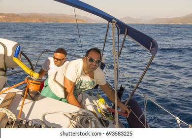 Men are hanging on the boat. One is looking down and the other is smiling to the camera