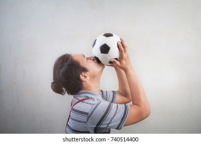 Men happy kiss a ball of football fan cheering