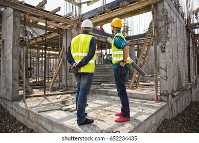 Men in hardhat and green jacket posing on building site.Film noise