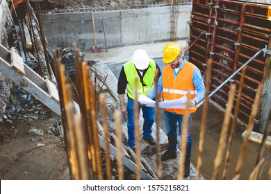 Men in hardhat and yellow and orange jacket posing on building site