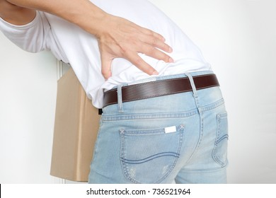 Men have back pain. muscle pain From lifting a heavy box. On a white background Health concepts and pain relief.;