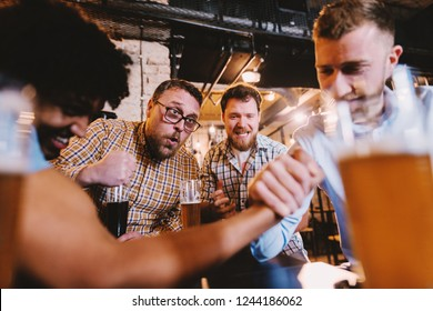Men having arm wrestling and their friends cheering. Pub interior, glasses of beer on table.