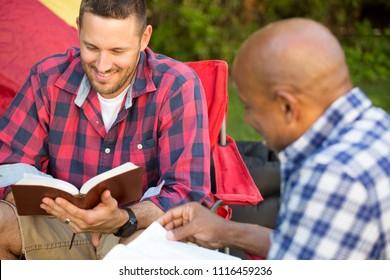 Men having a bible study on a camping trip.