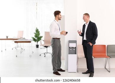 Men having break near water cooler at workplace. Space for text