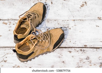 Men hiking shoes laying on white wooden board