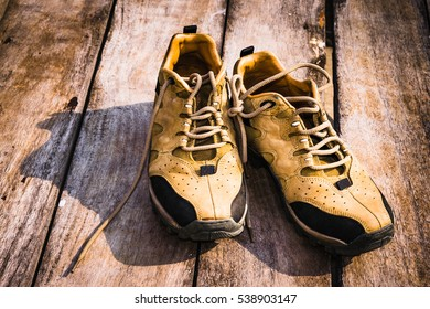 Men hiking shoes laying on wooden board